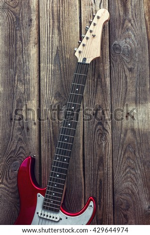 Red electric guitar on grunge wooden planks background. Place for text. Vertical. - stock photo