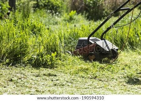 red electric lawn mower - stock photo