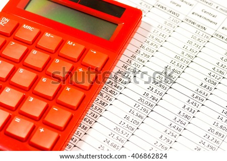 Red electronic calculator on spreadsheet - stock photo