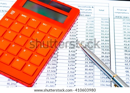 Red electronic calculator on spreadsheet with black clipboard - stock photo
