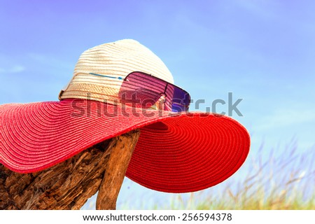 Red elegant women summer hat with sunglasses on blue sky background. Outdoors summertime close-up. - stock photo