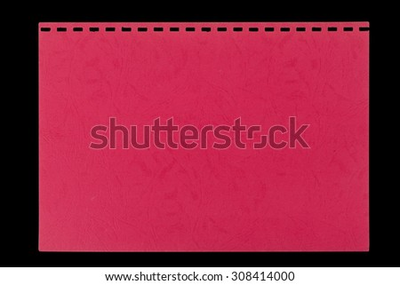 Red embossed sheet torn from a notebook, isolated against a black background. - stock photo