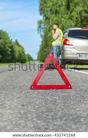 Red emergency sign on the road, male driver calling to a car assistance, spare wheel near broken car. - stock photo