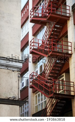 Red emergency staircase in a building facade. Vertical