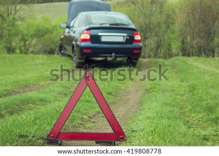 Red emergency stop sign and broken  car on the country  road