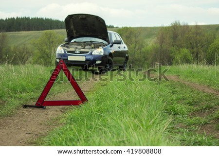 Red emergency stop sign and broken  car on the country  road - stock photo