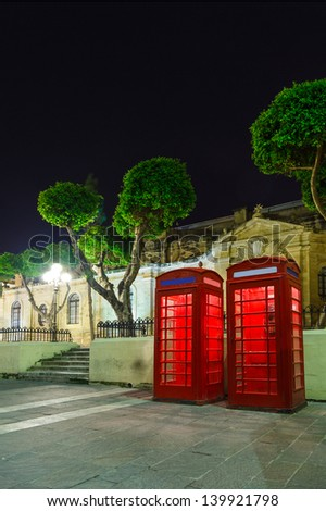 red English telephone box on Malta a summer night in the light of lanterns with trees