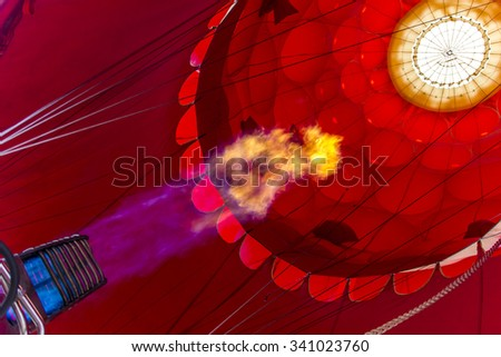 Red envelope of the hot air balloon with a fire from a burner - stock photo