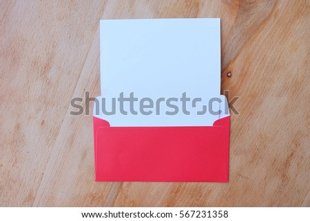 Red envelope with empty paper over wooden background