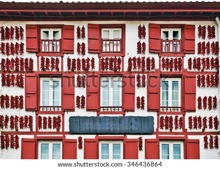 Red Espelette peppers drying in the wall of a traditional Basque house in Espelette village, Basque province of Labourd, France, Atlantic Pyrenees, Aquitaine  - stock photo
