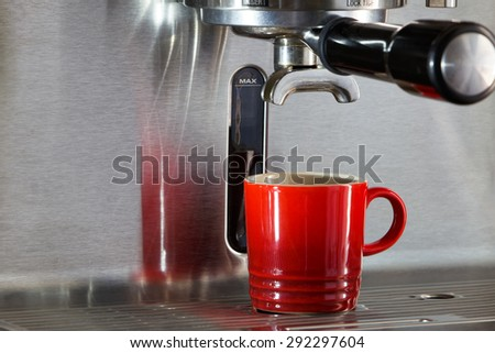 Red espresso cup on  steel, metallic espresso maker under the portafilter in anticipation of coffee dripping into the cup. Red cup is a nice juxtaposition against the gray steel of the machine. - stock photo