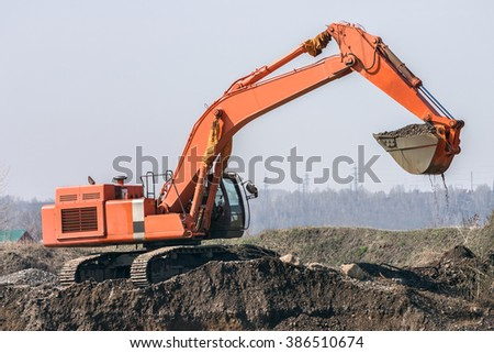 red excavator digs the ground