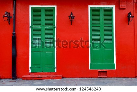 Red Exterior Wall With Green Shuttered Doors And Lanterns In New Orleans French Quarter - stock photo