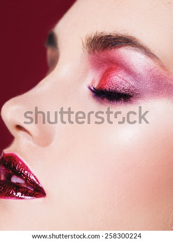 Red Eye Makeup. Beautiful eye makeup close up, bright lips - stock photo