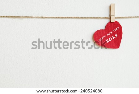 Red fabric heart with happy new year 2015 word hanging on the clothesline, new year template - stock photo