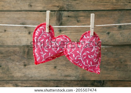 Red fabric Valentine hearts hanging on a line with clothes pegs over wooden boards.