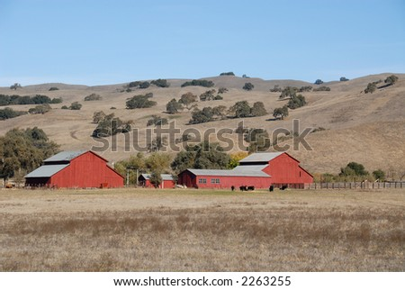 Red farm buildings against dry, parched hills, Morgan Hill, California