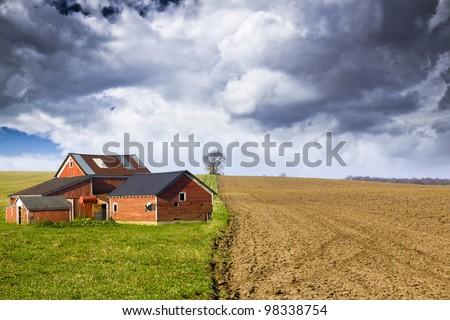 Red Farm with stormy sky - stock photo