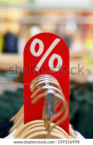 Red fashion sale label with wooden hangers in a row. Shallow depth of field. - stock photo
