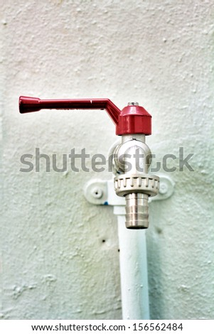 Red faucets and white wall