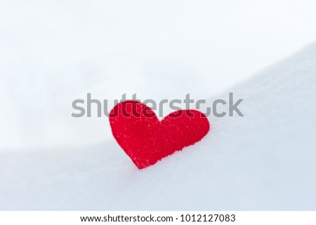 red felt heart figure on snow, winter day