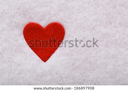 Red felt heart in white felt background - stock photo