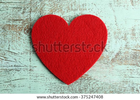 Red felt hearts on blue wooden background - stock photo