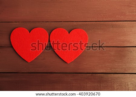 Red felt hearts on purple wooden background - stock photo