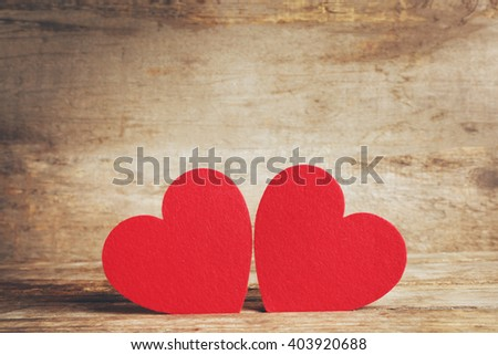 Red felt hearts on wooden background - stock photo