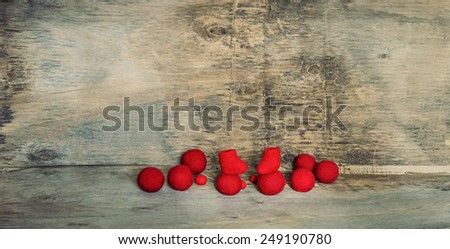 red felted beads and boots on the wooden background - stock photo