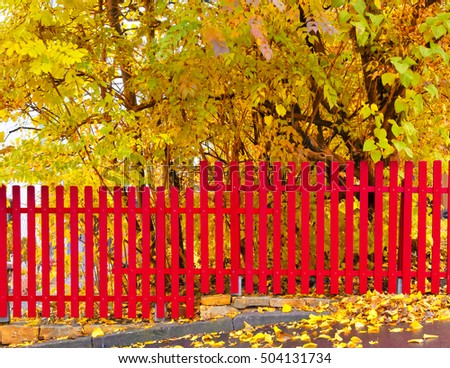 Red fence on a garden in fall
