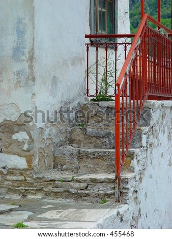 Red fence on the steps of a house in Samos, Greece