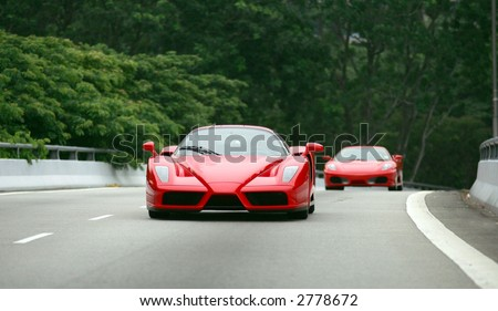 Red Ferrari Enzo and F430 on the road in Singapore - stock photo