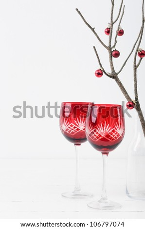 Red festive christmas wine glasses on table with minimalist christmas tree - stock photo