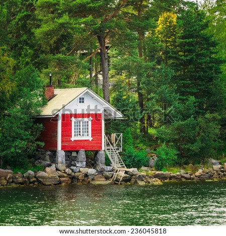 Red Finnish Wooden Sauna Log Cabin On Island In Summer - stock photo