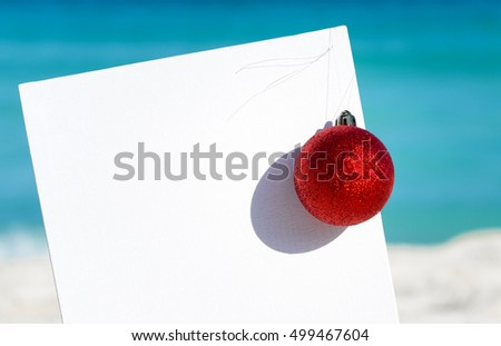 Red fir tree decoration ball near blank paper board on sandy beach, Tropical christmas and New Year celebration