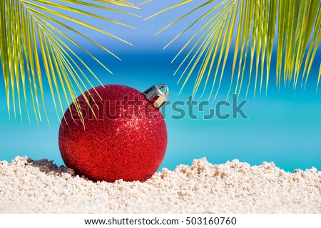 Red fir tree decoration ball on sandy beach with palm tree leaves, Tropical christmas and New Year celebration