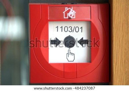 red fire alarm button with blurry background