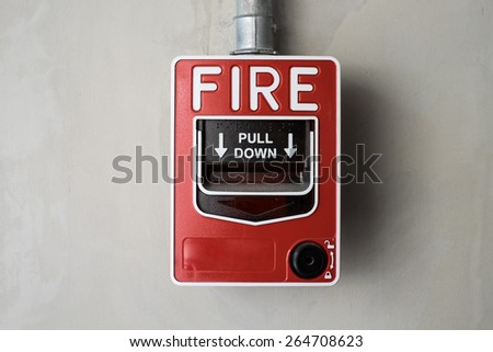 red fire alarm on  cement background