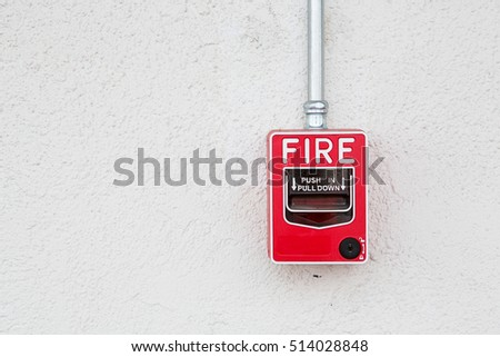 Red fire alarm switch at white wall