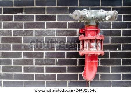 Red fire hydrant in the black brick wall - stock photo