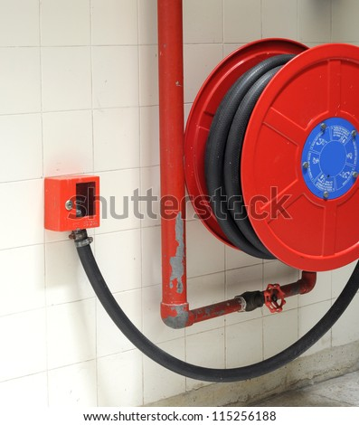red fire hydrant reel on a wall - stock photo