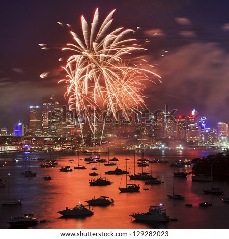Red Fire palm tree during firework in Sydney new year eve event celebration bright pyrotechnic lights reflect in harbor water over city CBD