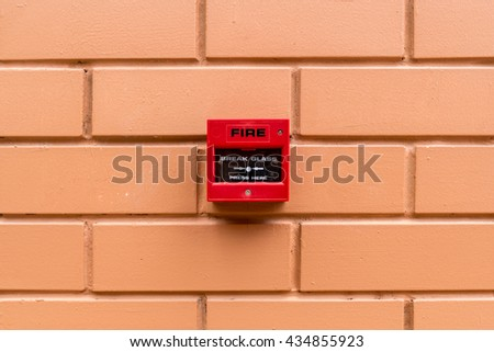 Red fire switch on brown brick wall