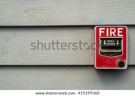 Red fire switch on wooden wall - stock photo