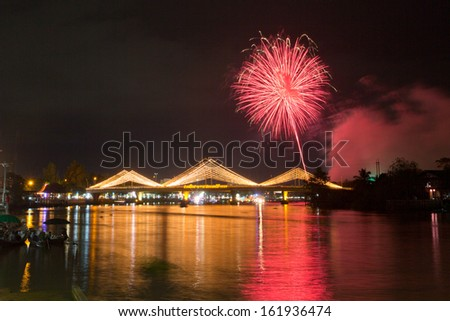 red firework over the bridge in Suratthani, Thailand.