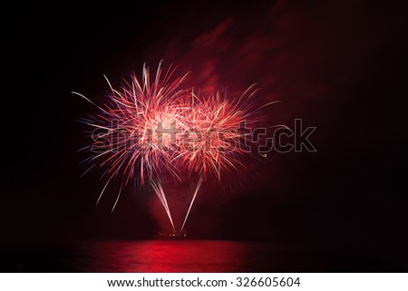 Red fireworks in the night sky over water - stock photo