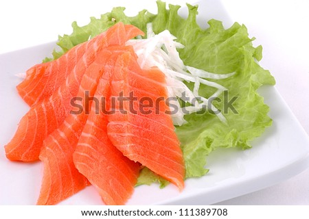 Red fish cut with slices on a dish with vegetables - stock photo