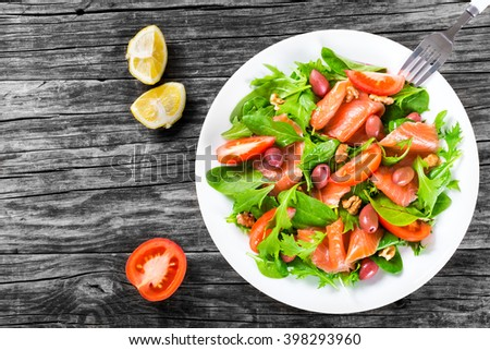 Red fish healthy salad with mixed lettuce leaves, olives and tomatoes on a white dish on a old rustic table, easy recipe, top view - stock photo