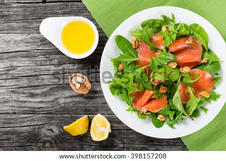 Red fish healthy salad with mixed lettuce leaves on a white dish on a old rustic table, easy recipe, top view - stock photo
